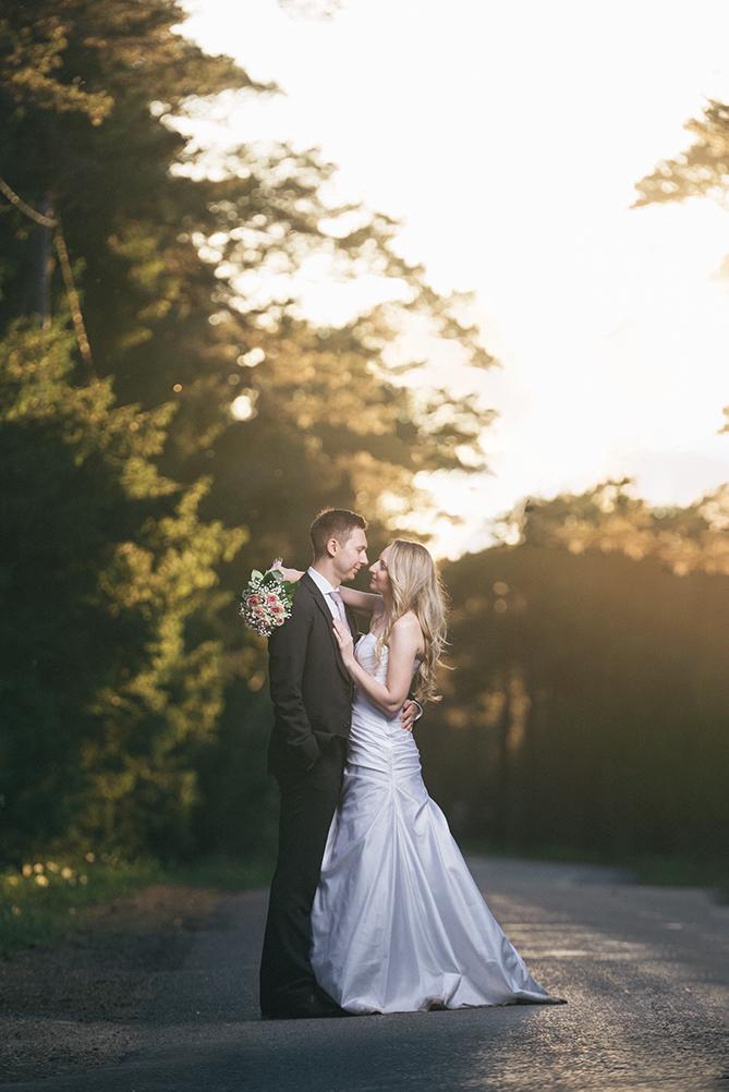 Pruutpaar kallistamas maanteel päikseloojangus