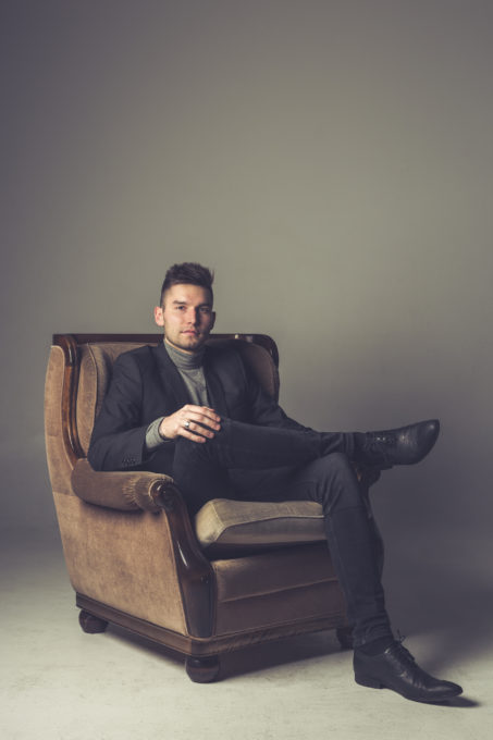 Ülikonnas tugitoolil istuv mees